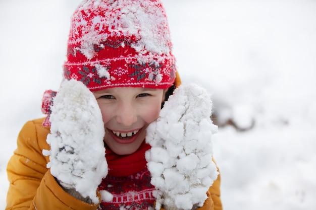 雪に覆われたミトンで冬の幸せな少年。
