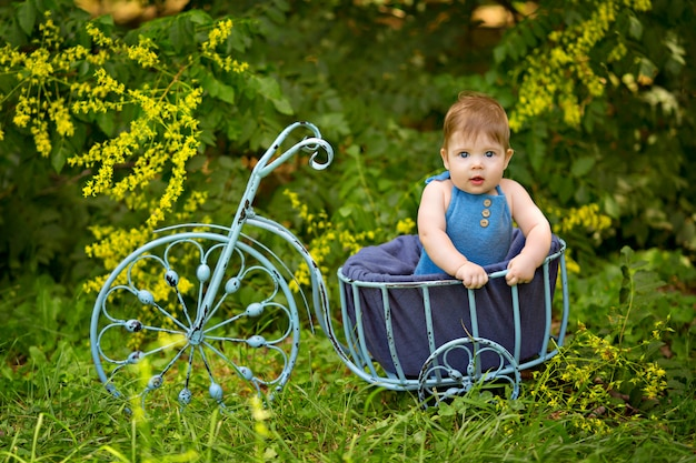 Happy little boy infant 8-12 months old sitting in a toy bike on nature.