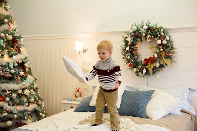 Happy little boy jumping on bed. little boy having fun celebrating christmas at home