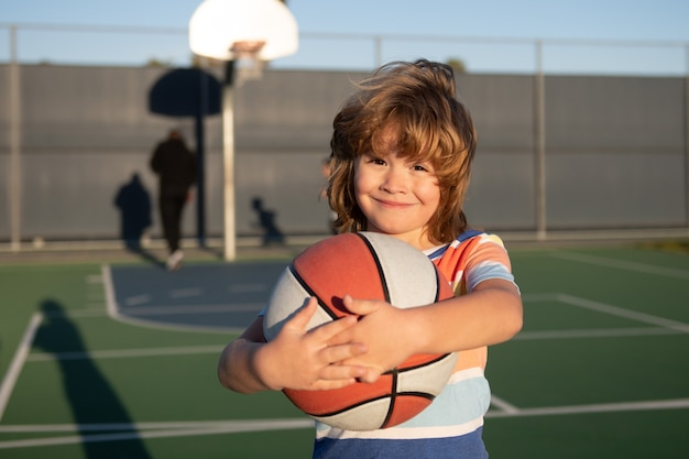 Happy little boy kid playing basketball on playground