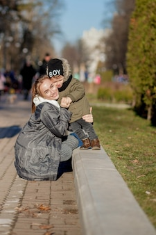 Happy little boy kissing mother outdoors