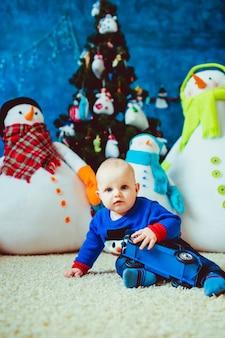 Felice piccolo ragazzo vicino pupazzo di neve giocattolo in studio