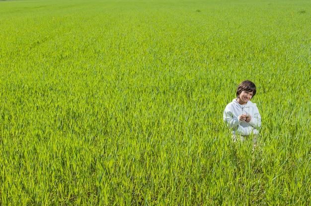 美しい緑色の黄色の草の牧草地で幸せな少年
