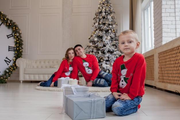 Счастливый маленький мальчик открытия рождественских подарков около нового года.