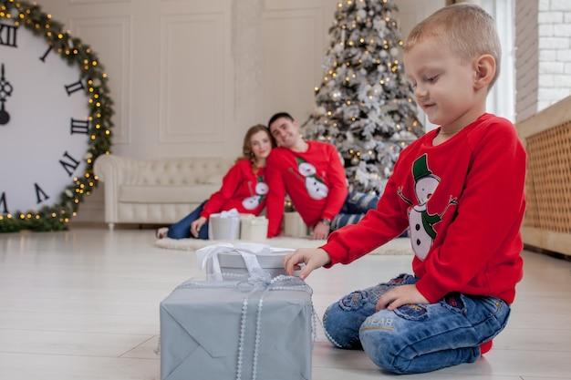 Счастливый маленький мальчик открывает рождественские подарки перед новым годом