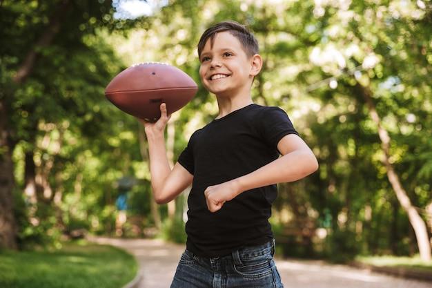 公園の自然の中で屋外の幸せな男の子がラグビーをプレイ