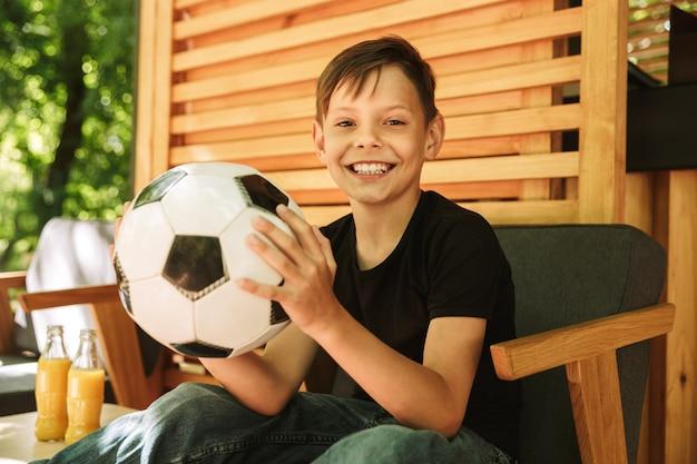 サッカーを保持しているカフェ自然に屋外に座って幸せの小さな男の子