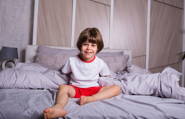 A happy little boy in pajamas is sitting on cotton bedding on the bed in the bedroom