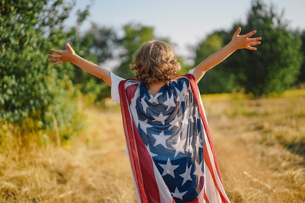 Happy little boy patriot running in the field with american flag. usa celebrate 4th of july