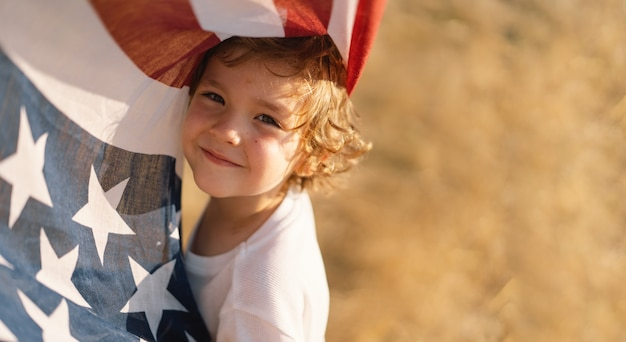 Счастливый патриот маленького мальчика, работающий в области с американским флагом. сша празднуют 4 июля