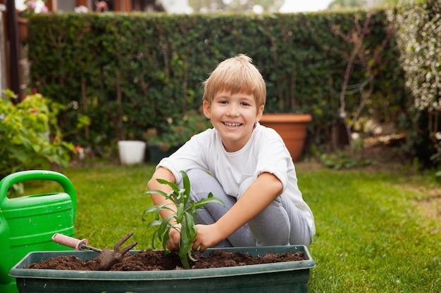 Счастливый маленький мальчик сажает и выращивает цветы