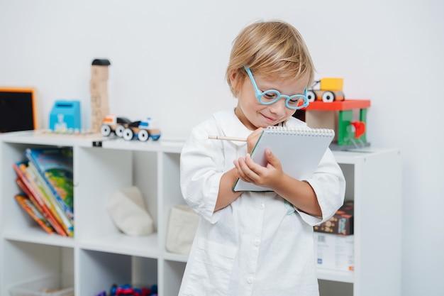 Счастливый маленький мальчик играет доктора в игрушечных очках и белом халате