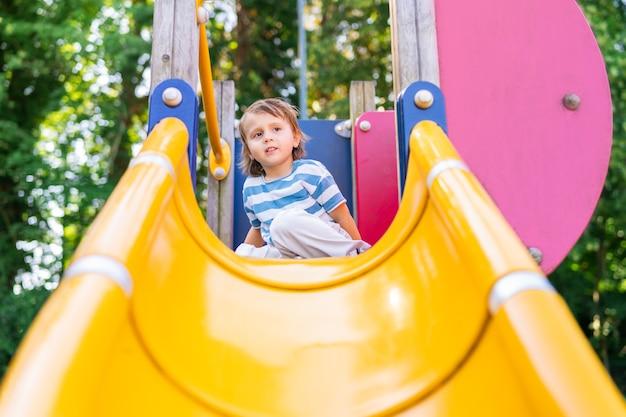놀이터에서 공원에서 노는 행복한 어린 소년. 슬라이드에 앉아 멀리 보고 유아입니다. 어린이를 위한 여름 활동.
