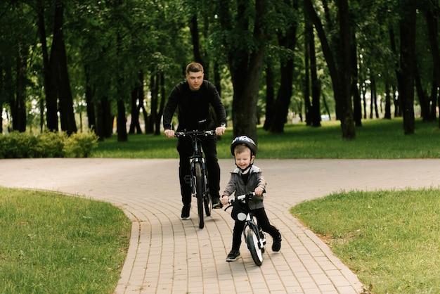 幸せな少年は公園で若いお父さんと一緒に自転車に乗る