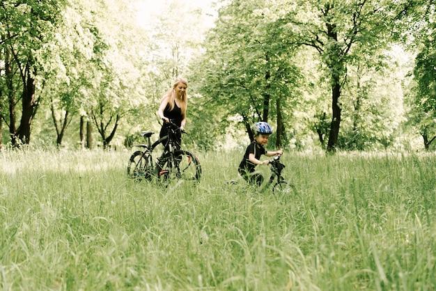 幸せな少年が公園で若いお母さんと一緒に自転車に乗る