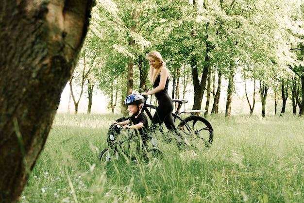 幸せな少年は公園で若いお母さんと一緒に自転車に乗る
