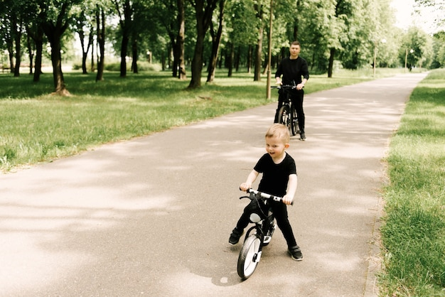 Happy little boy rides a bike with a young dad in the park