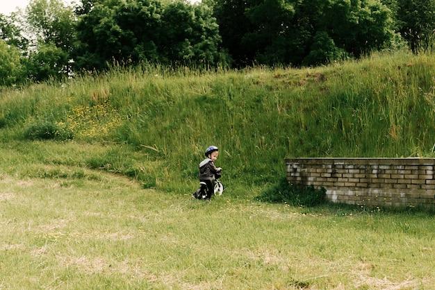 Счастливый маленький мальчик на велосипеде в парке