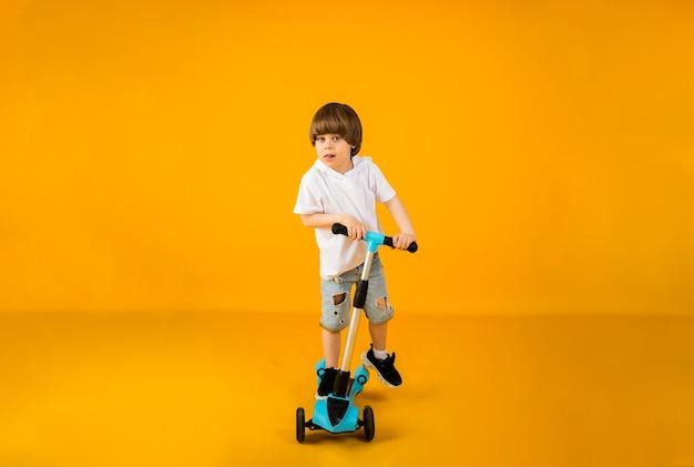 텍스트에 대 한 공간을 가진 노란색 표면에 스쿠터를 타고 행복 한 어린 소년