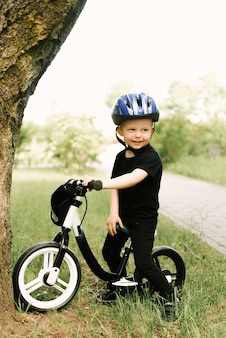 Happy little boy riding a bike running in the park