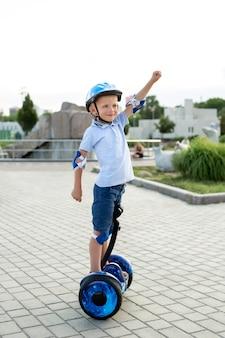 공원에서 호버 보드 또는 스쿠터를 타고 행복 한 어린 소년