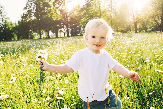 Счастливый маленький мальчик, бегущий на лугу цветов с букетом диких ромашек