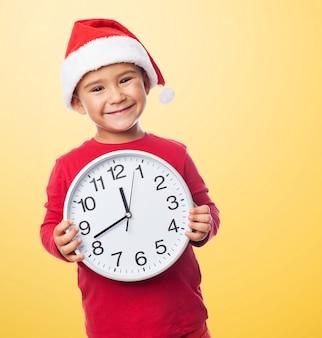 Happy little boy showing a clock