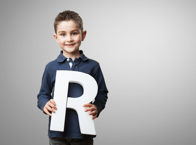 Happy little boy showing the letter r