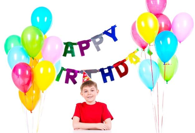 Счастливый маленький мальчик сидит за столом, развлекаясь на вечеринке по случаю дня рождения - изолированный на белом