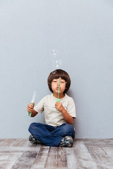Happy little boy sitting and blowing soap bubbles