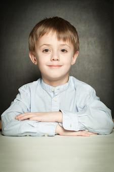 학교 교실에 앉아 있는 행복한 어린 소년