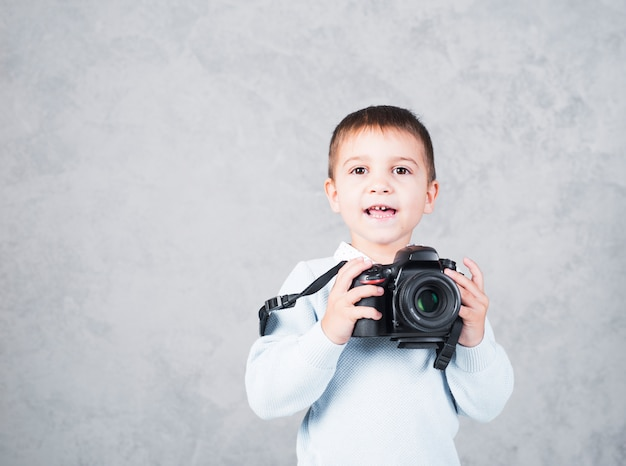Happy little boy standing with camera