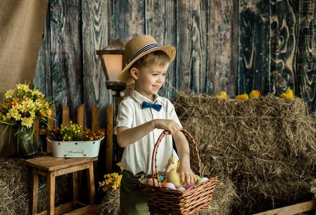행복 한 어린 소년 약자와 다채로운 계란 바구니를 보유하고있다. 에그 헌트