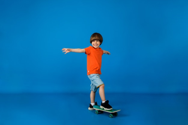 Happy little boy stands with a skateboard on a blue surface with space for text