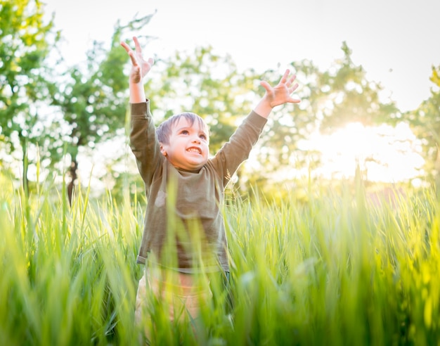 Happy little boy on summer meadow having fun and happy time