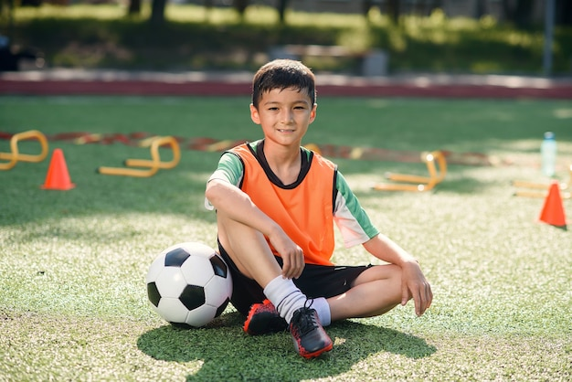 Happy little boy in uniform sitting on soccer field with a ball