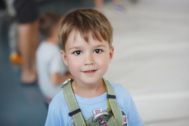 행복 한 어린 소년 등반 안전 벨트를 착용