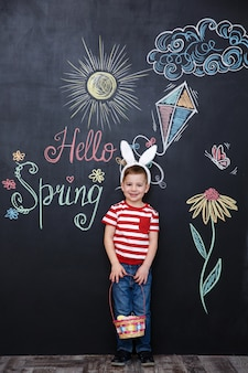 Happy little boy wearing bunny ears and holding easter basket