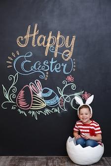 토끼 귀를 착용하고 큰 금이 달걀 껍질 안에 서 행복 한 소년