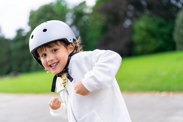 安全ヘルメットをかぶった幸せな少年。公園を歩いている笑顔の子供の肖像画を閉じます。