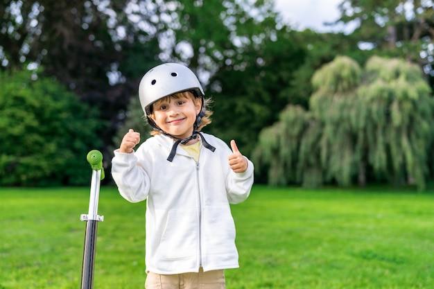 キックスクーターの近くにいる安全ヘルメットをかぶった幸せな少年。公園を歩いている笑顔の子供の肖像画を閉じます。