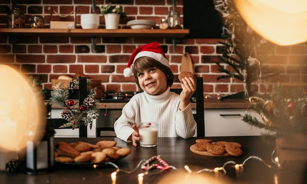 A happy little boy in a white sweater and a new year's hat is sitting in the kitchen with a glass of milk and oatmeal cookies