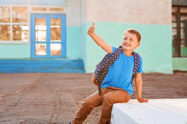 Happy little boy with backpack shows gesture of victory