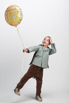 白い背景の上の風船、スタジオショットで幸せな小さな男の子