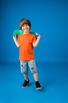 Happy little boy with brown hair holds a skateboard on a blue surface with space for text