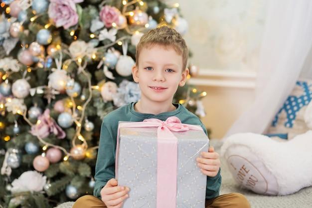 クリスマスプレゼントと幸せな男の子。少年は贈り物に喜んだ。