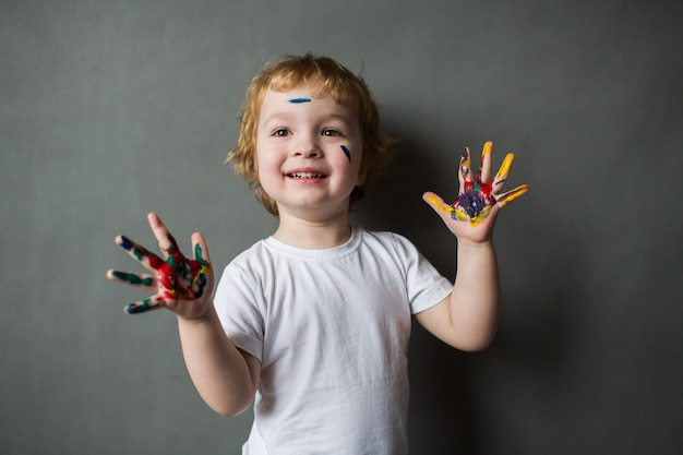 Happy little boy with colored hands, young artist