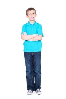 白い背景の上に立って全身カメラを見て交差した手を持つ幸せな少年。