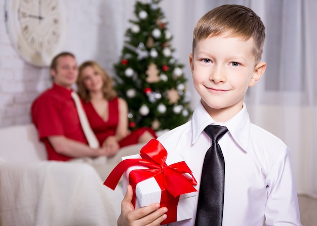 Happy little boy with gift from his parents and christmas tree