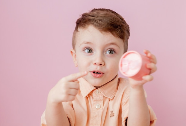 Happy little boy with a gift . photo isolated on pink background. smiling boy holds present box.